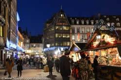 Christmas market near the cathedral of Strasbourg with famous Kammerzel house in background