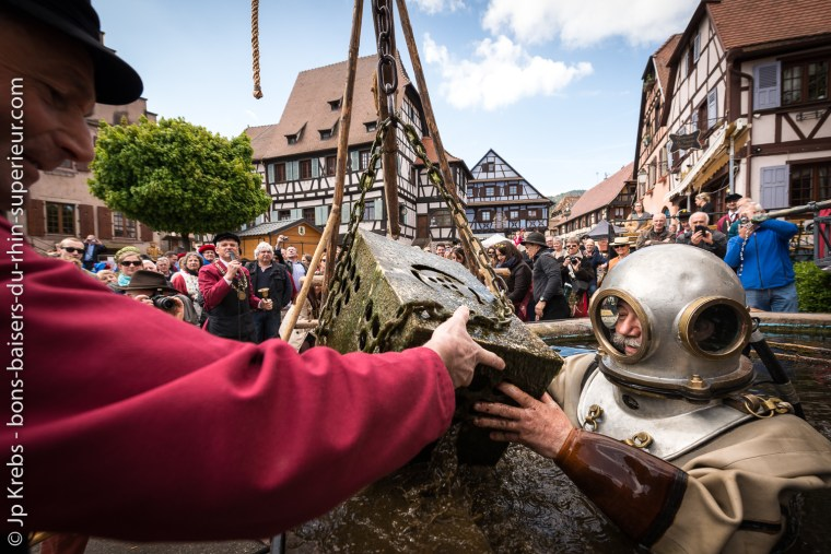 The diver collects the Bienheureuses (Blessed), bottles of the wine of the Brotherhood which spent a year in the depths of the fountain of the Bear in Dambach-la-Ville.