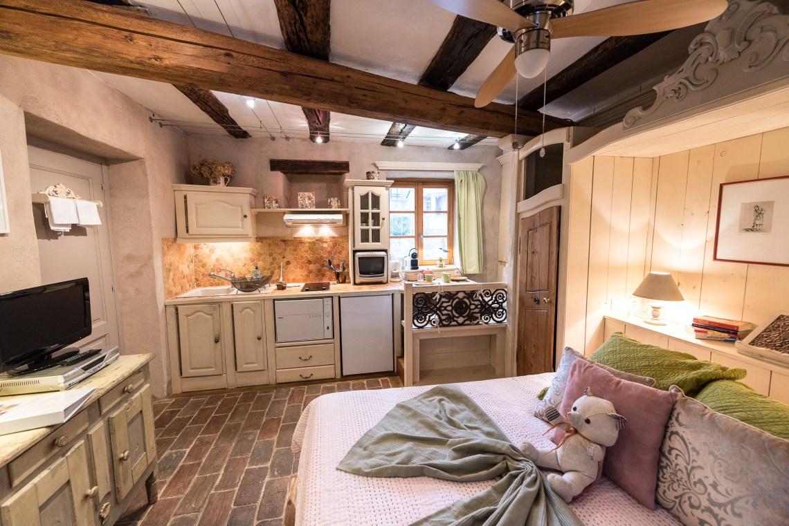 The Bed and the kitchen of The Gobelin's romantic Studio, charming studio with great comfort and Large double bed in Riquewihr for 2 persons