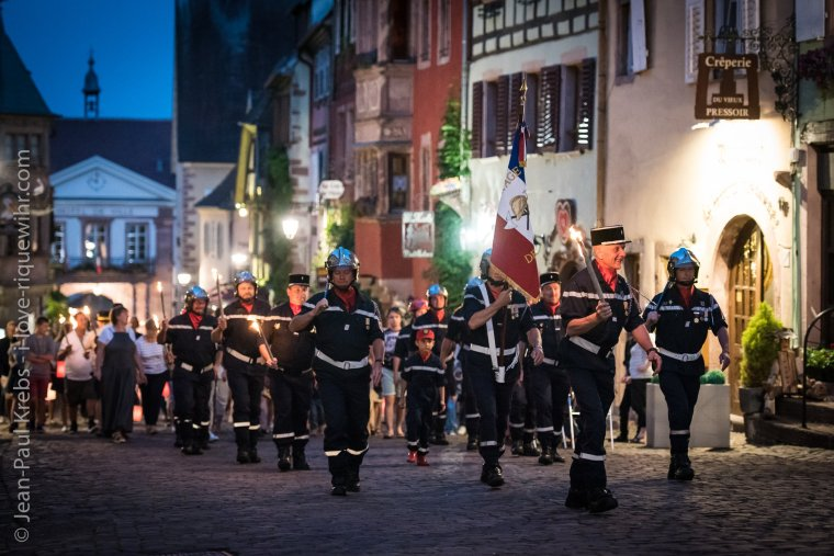 Firefighters parade with torches on July 13 at dusk in Riquewihr in Alsace.