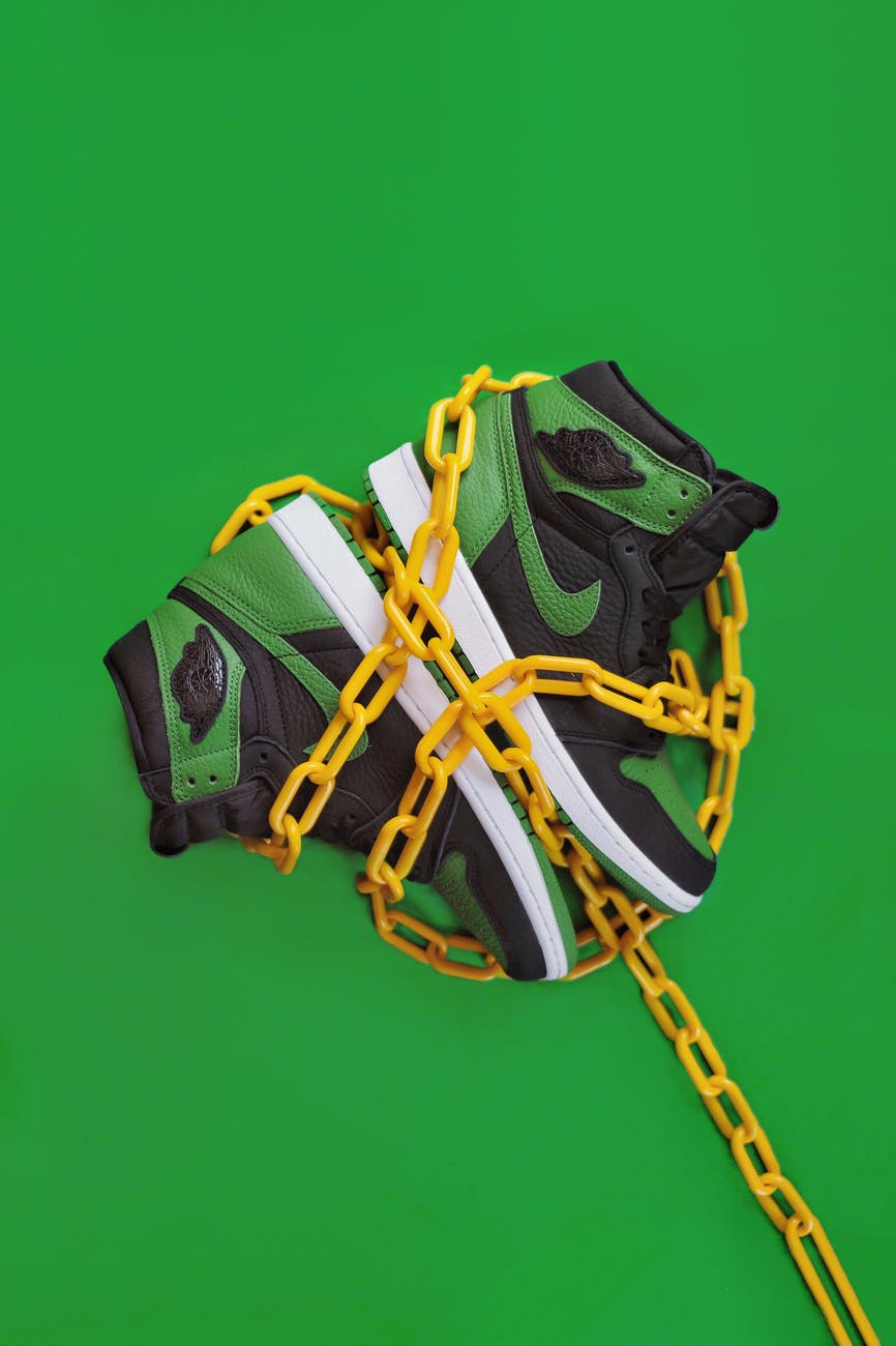 stylish sporty boots chained on green surface