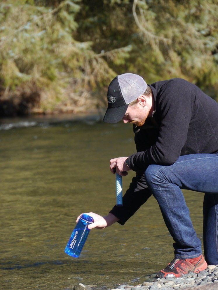 Lifestraw go being filled, the Lifestraw bottle is the absolute best filtered water bottle. A man is standing besides a lake filling the Lifestraw go bottle.