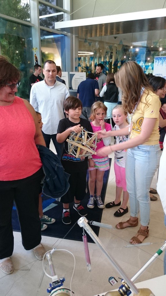 """BEST Labber Mallory Daly explains """"tensegrity"""" to a group of children at the 2016 Robot Block Party"""