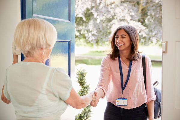 senior woman greets care worker