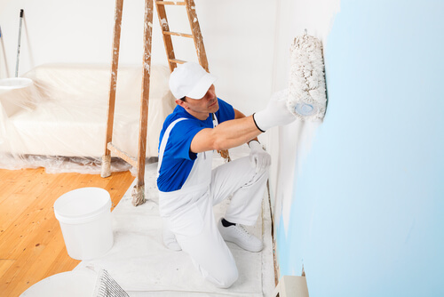 Man painting over blue wall with white paint from painting roller