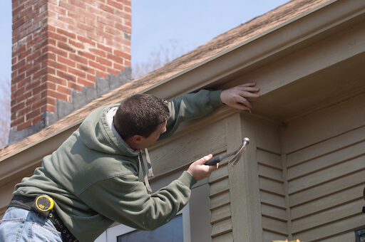 Man hitting nail into bottom of roof with hammer