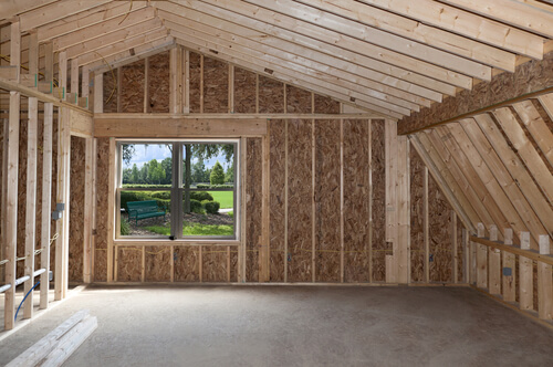 Inside of empty unfinished house with wood walls and columns