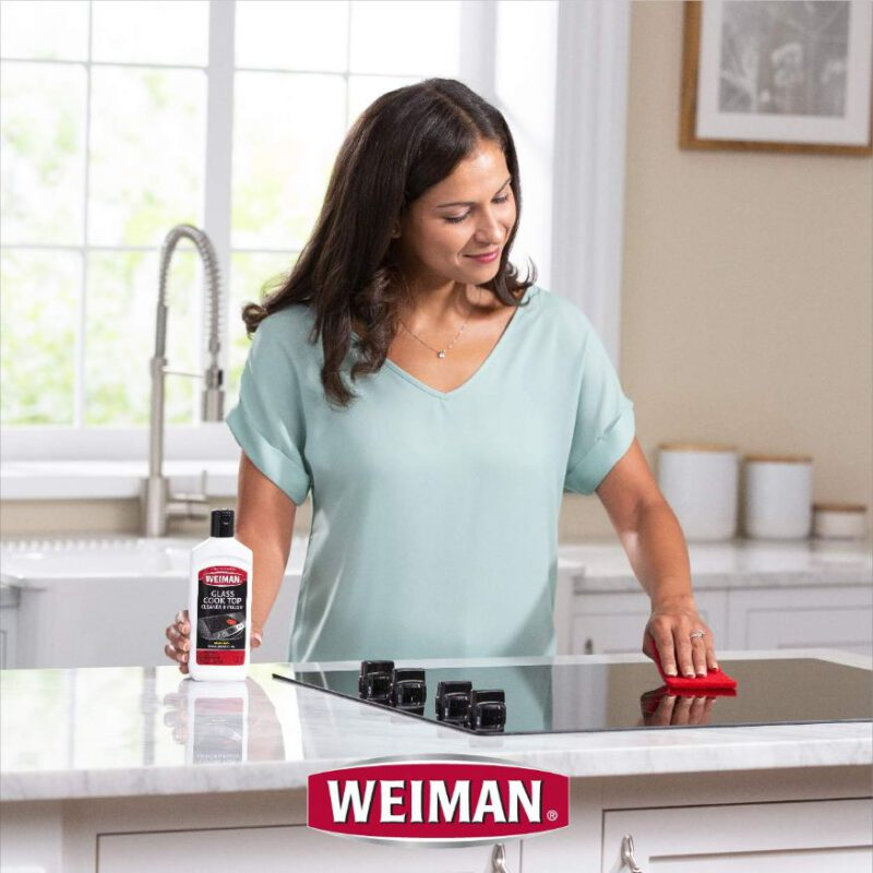 A Women Cleaning stove top with Weiman Best glass cooktop cleaner