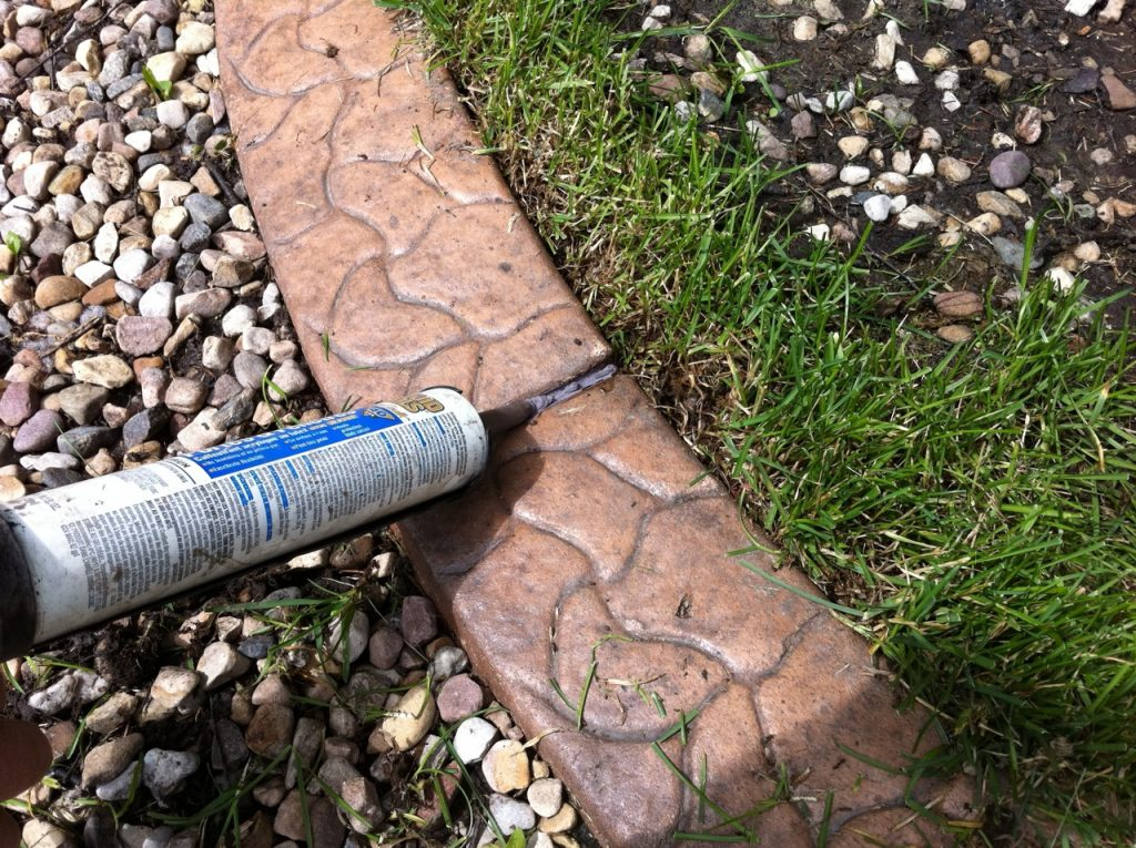 fill the gaps with caulking a shade darker than the curb