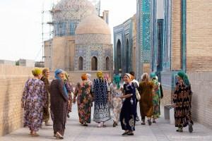 Oezbeekse vrouwen in kleurrijke jurken wandelen tussen de betegelde tombes in Samarkand