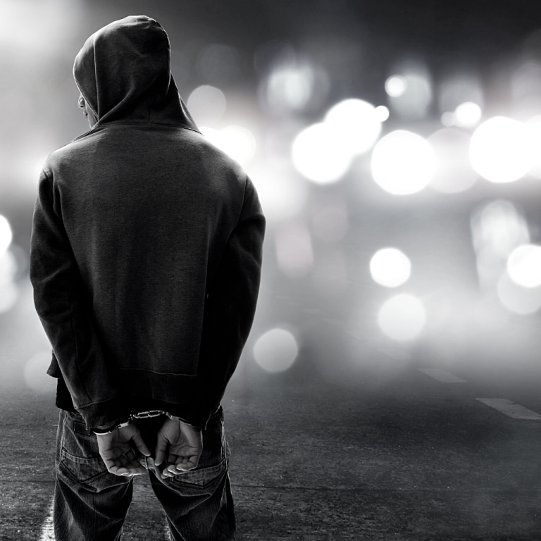 Author Kelly Underwood - Man in hoodie handcuffs with police lights in background