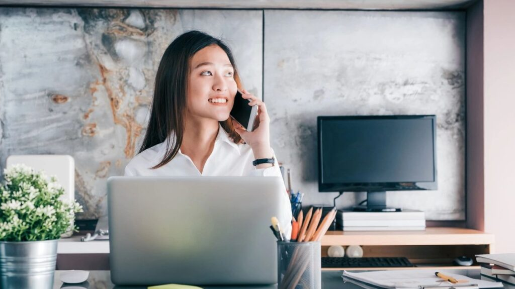 Woman in office at computer talking on phone