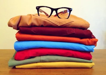A pile of clothes with glasses on them, you should get rid of the clothes you do not need any more while you are moving from NYC to Florida