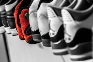Sneakers lined on a shelf.