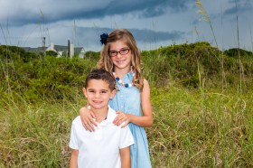 Little girl with glasses and her little brother getting pictures in Myrtle Beach
