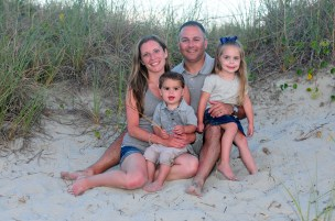 Small family in the sand dunes getting beach portraits