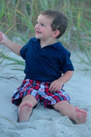 Little boy playing in dunes on the beach