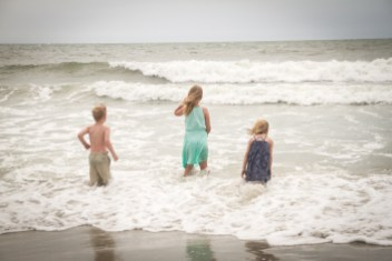 children playing in the ocean catching waves