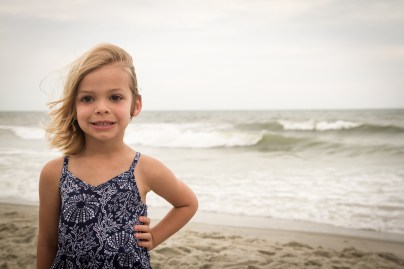 Little girl on the beach getting her picture taken