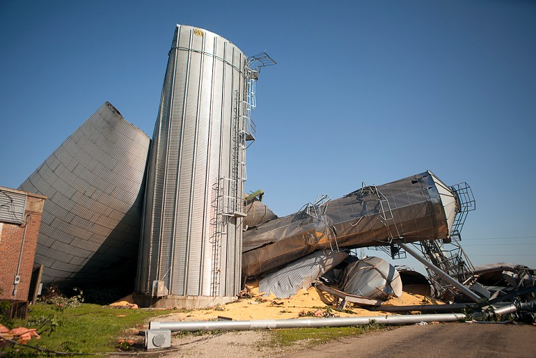 Multiple grain bins lie toppled over each other the morning after a tornado struck Cameron. STEVE DAVIS/The Register-Mail