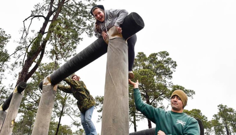 "Medford High School intern Sarah Shoemaker, center, receives a helping hand from a Marine, right, as she tries the obstacle ""Dirty Name"" as part of the Confidence Course when teachers from around New England got a chance to experience what life would be like for Marine recruits during the Marine Corps Educator Workshop at Parris Island in South Carolina on Wednesday, Feb. 25, 2015."