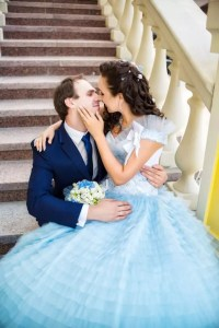 happy husband kisses his young wife on the stairs