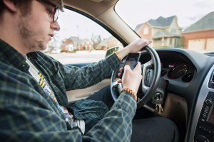 young man texting and driving distracted