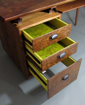Surprise! The somber exterior is relieved by the whimsy of brightly-tinted tamo ash drawers.