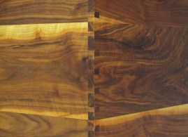 A detail of dovetails and swirling wood grain.