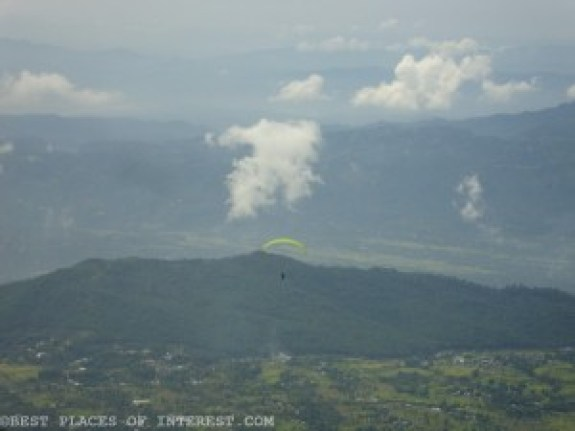a paraglider flying over the valley.