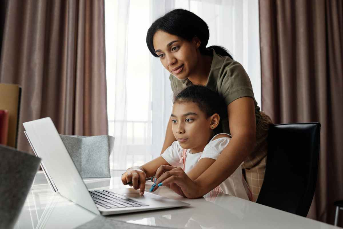 mother helping her daughter use a laptop