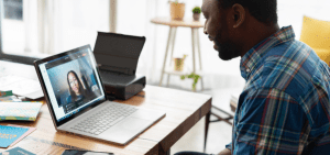 A man is in a virtual meeting with a woman.