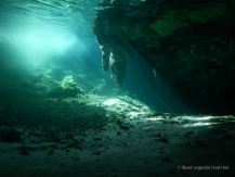 Sun rays peeping through the water and lighting up a stalactite