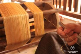 Eliminating imperfections on the golden silk thread by hand, Siem Reap, Cambodia