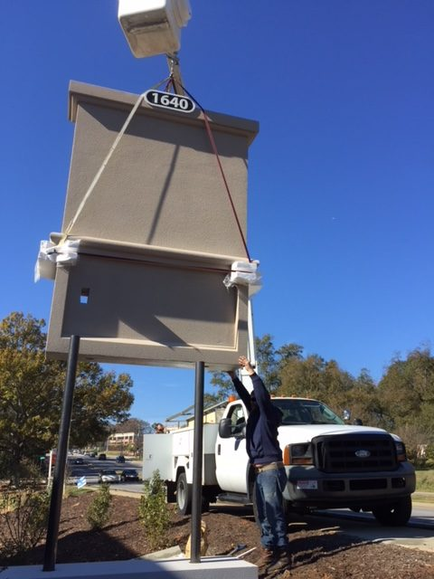 Stucco sign monument being lifted in the air during installation.
