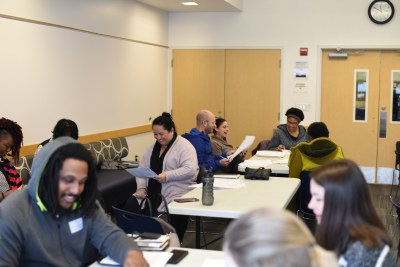 Photo from 2020 Data Storytelling Workshop shows three multiracial groups of people sitting at tables and conversing on a workshop activity.