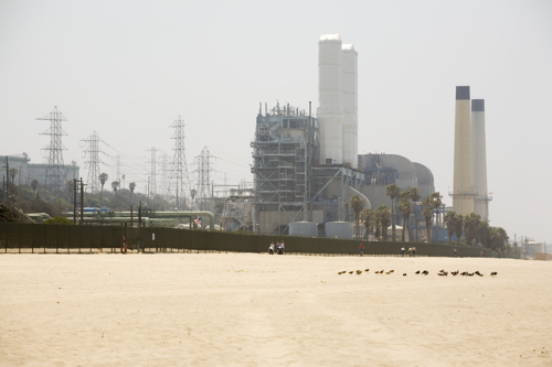 beach with oil refinery