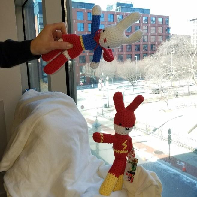 Crocheted Superbunnygirl and Flashbunny speeding across a chemo window