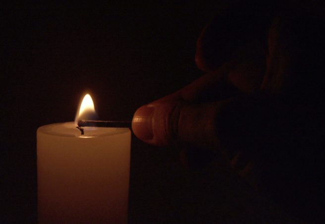 a hand lighting a candle