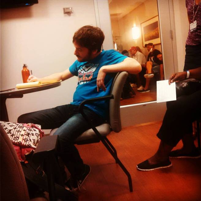 Jarrod sitting in a chair, taking notes at chemo class