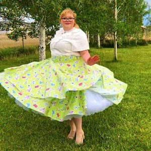 Beautiful woman twirls in a white blouse and crinoline in her grean wrap skirt