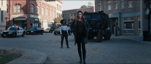 Image Description: Wanda Maximoff, wearing a hoodie, walks away from Monica Rambeau. Behind them are a tank, police vehicles, and the facades of brick town buildings.