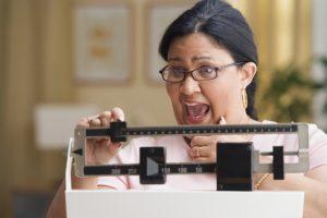 Shocked woman weighing herself