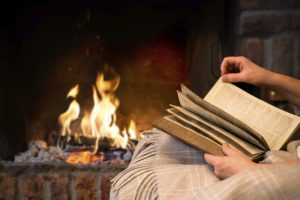 reading book by fireplace