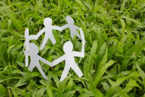 Paper people in a circle with green grass background