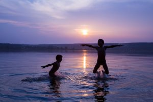Two boys jumping into water on sunset