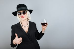 Charming senior woman smiling and drinking wine.
