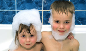 Two little children in a bathtub with shampoo foam