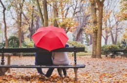 elderly retired couple sitting together on the bench in autumn park, love concept