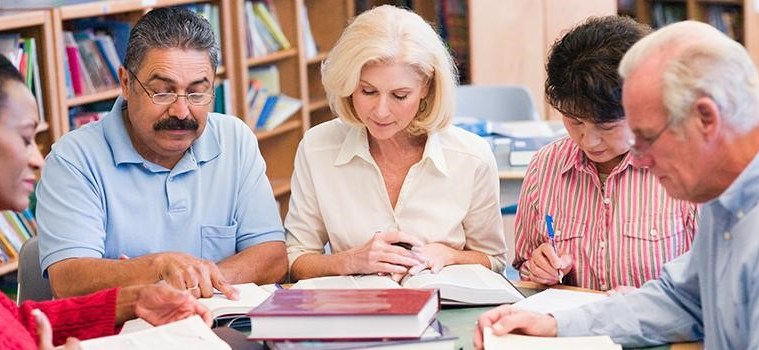 Group of adults learning in library